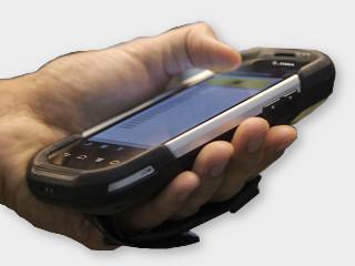 Le terminal monile de lecture de tag RFID dans la main de l'utilsiateur scannannt des étiquettes RFID pour la traçabilité industrielle